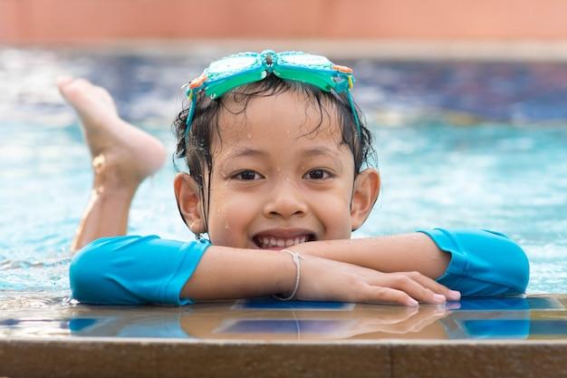 Het kindmeisje van de glimlach met beschermende brillen in zwembad.