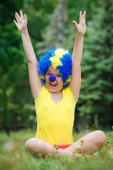 Het kindmeisje van het kind met blauwe de pruiken grappige gelukkige open wapensuitdrukking en slingers van de partijclown in het park