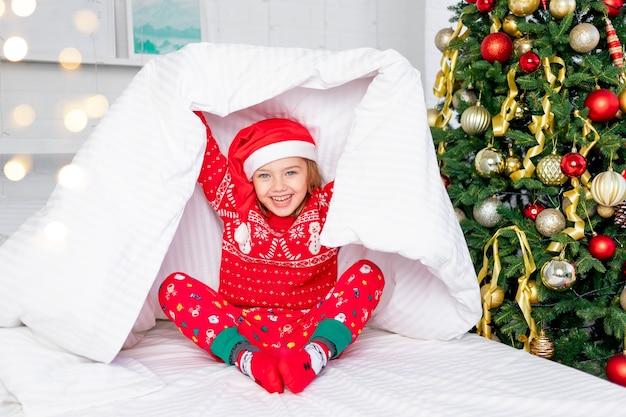 Het kindmeisje werd wakker onder de boom in een rode trui en een kerstmuts op oudejaarsavond of kerstmis in een wit bed met een sneeuwpop in haar armen die onder de deken uitkeek en glimlachte