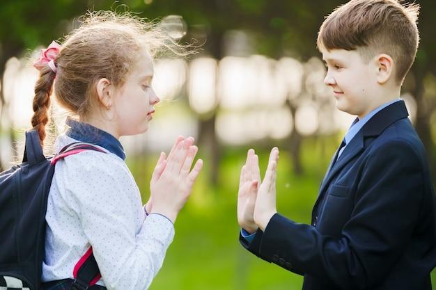 Het kindvriend die van de school geniet van slaande handen