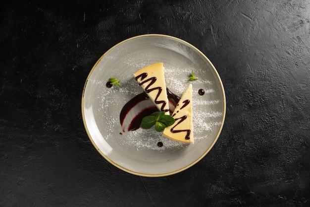 Het klassieke dessert - twee plakjes cheesecake met bessensaus, gegarneerd op een zwarte stenen tafel