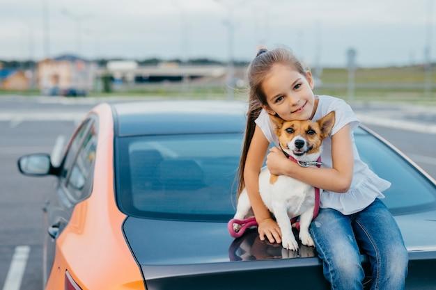 Het kleine aantrekkelijke vrouwelijke kind omhelst haar favoriete hond, zit samen bij boomstam van auto