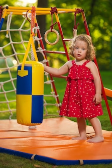 Het kleine babymeisje dat bij openluchtspeelplaats speelt