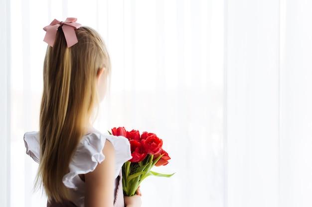 Het kleine boeket van de meisjesholding van rode tulpenbloemen. concept voor wenskaart