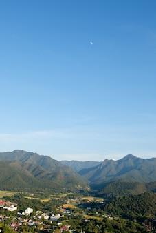 Het kleine dorpje aan het einde van de landingsbaan ligt in de vlakte tussen de bergketen, uitzicht vanuit het gezichtspunt van de tempel op de hoge berg, boven uitzicht met de kopieerruimte.