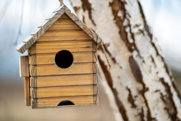 Het kleine houten vogelhuis hangen op een boomtak in openlucht.