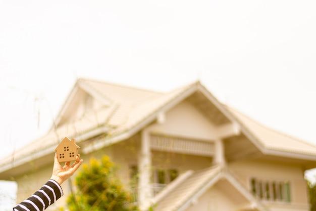 Het kleine huismodel in vrouwenhand ziet uit op een huis