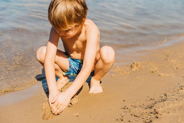 Het kleine jongen spelen met zand op strand