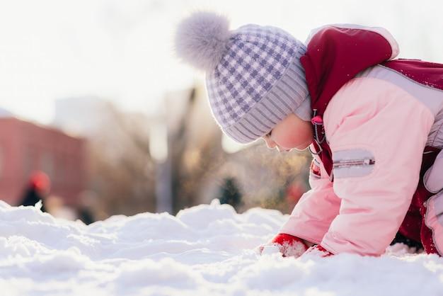 Het kleine kind kruipt op sneeuw tegen de achtergrond van een zonsondergang in de winter