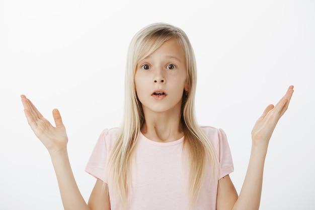 Het kleine kind weet niets, heeft geen idee en weet niet hoe te handelen in een moeilijke situatie. binnen schot van verontrust bezorgd schattig meisje met blond haar, schouderophalend en handpalmen opheffend, zonder idee