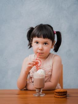 Het kleine kindmeisje drinkt hete chocolade of cacao met koekjes door een cocktailbuis op grijs