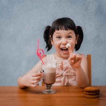 Het kleine kindmeisje drinkt hete chocolade of cacao met koekjes door een cocktailbuis.