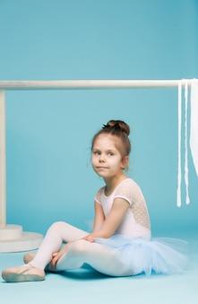 Het kleine meisje als balerina danser zitten en poseren in de buurt van ballet rek op blauwe studio