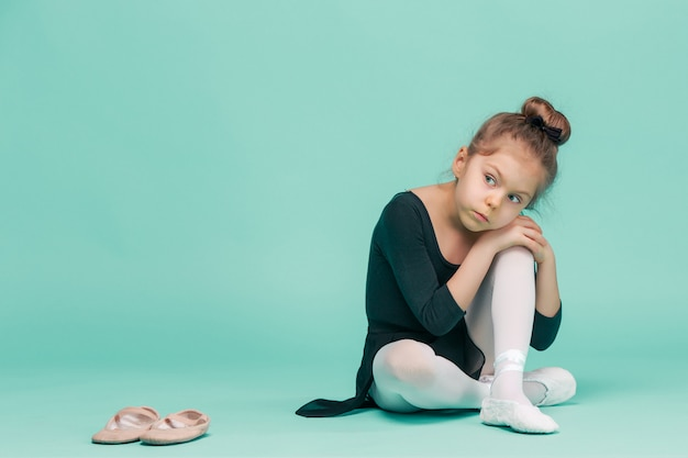 Het kleine meisje als balerina danser zittend op witte houten stoel op blauwe studio