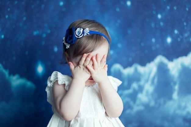 Het kleine meisje bedekte haar gezicht met haar handen tegen de roze achtergrond. boos meisje met losse haren op het hoofd van de band met de oren van een kat.
