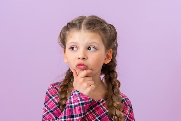 Het kleine meisje denkt na over een interessant idee en kijkt weg.