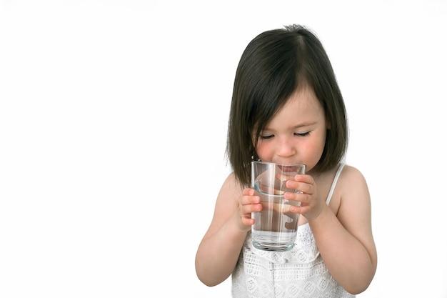 Het kleine meisje drinkt water uit een glazen beker.