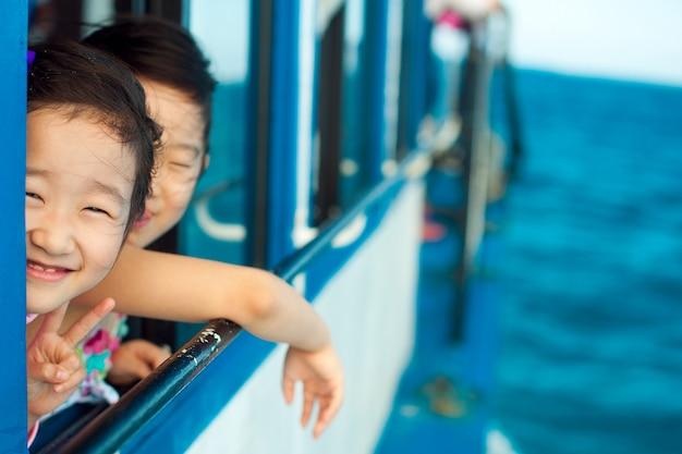 Het kleine meisje glimlacht verlegen naar de camera en opent het raam in de boot op de koele zomerzee.