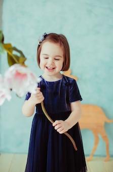 Het kleine meisje houdt bloemen in de kamer