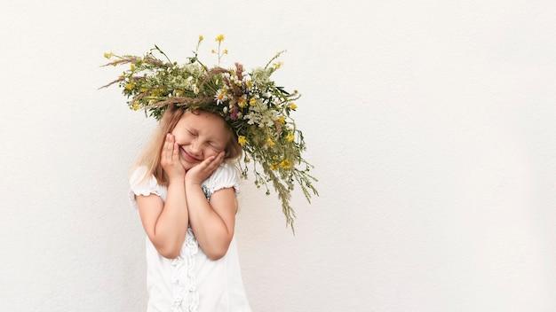 Het kleine meisje in de bloemenkrans legde haar handen voor haar gezicht en sloot haar ogen
