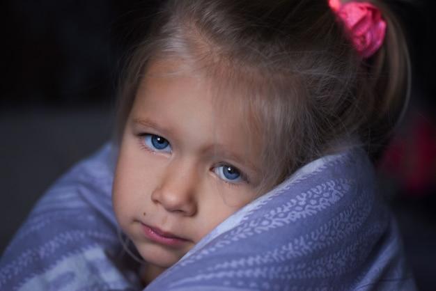 Het kleine meisje is ziek en ligt onder de dekens in bed