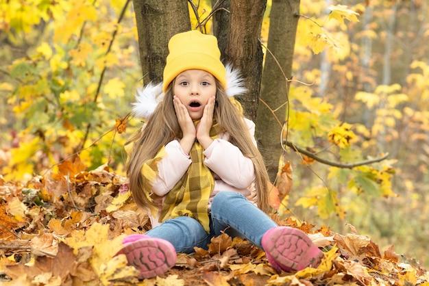 Het kleine meisje kijkt verbaasd naar de herfst.
