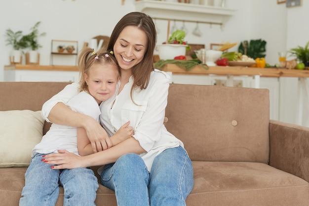 Het kleine meisje klaagt bij haar moeder en huilt. een jonge vrouw kalmeert haar dochter op de bank thuis.