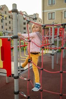 Het kleine meisje klimt touwen op de speelplaats