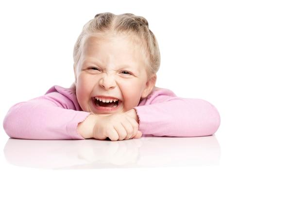 Het kleine meisje lacht besmettelijk. geã¯soleerd op witte achtergrond.