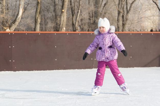 Het kleine meisje lacht en schaatst op het ijs.