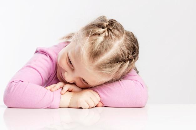 Het kleine meisje legde haar hoofd op de tafel. witte muur. detailopname.
