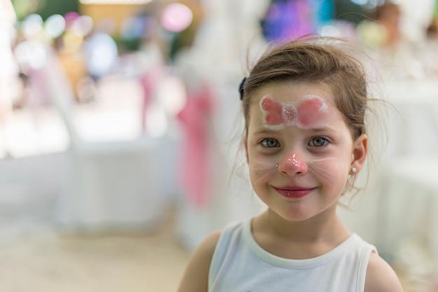 Het kleine meisje met gezicht schilderde met een vlinder die bij de camera glimlacht