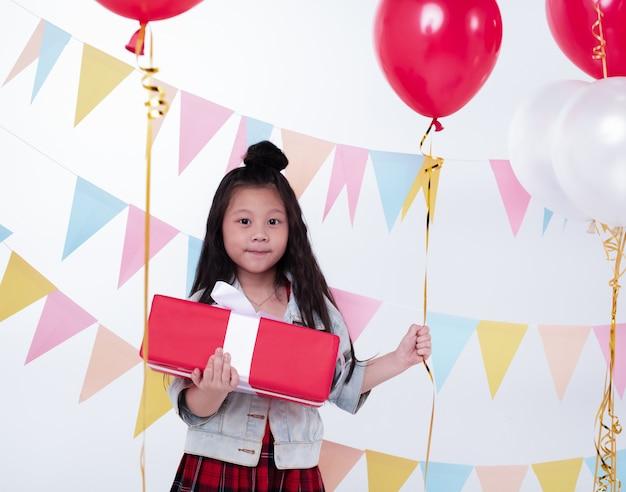 Het kleine meisje met rode geschenkdoos met rechter arm en houd rode ballon met de linkerhand