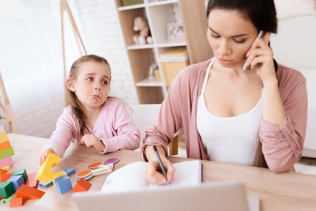 Het kleine meisje mist haar moeder terwijl ze aan het telefoneren is