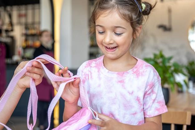 Het kleine meisje onderzoekt de rugzak die haar werd aangeboden.