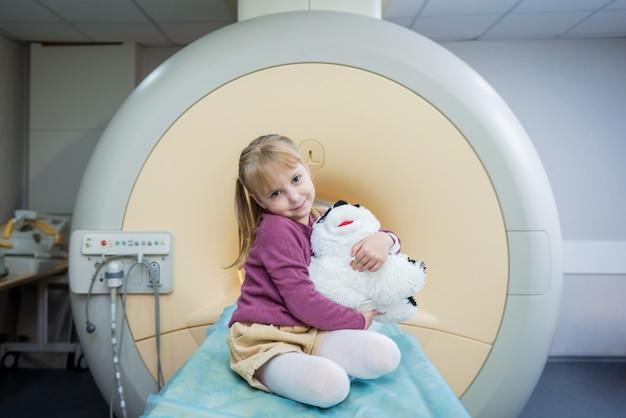 Het kleine meisje poseren op camera vóór mri hersenonderzoek