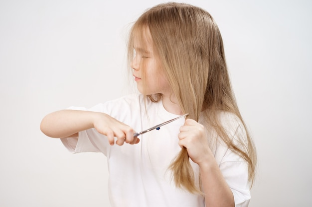 Het kleine meisje scheert haar lange haar met een schaar en bang op een witte achtergrond. modieus kapsel voor de baby. kapper. grappen van kinderen. kapsel