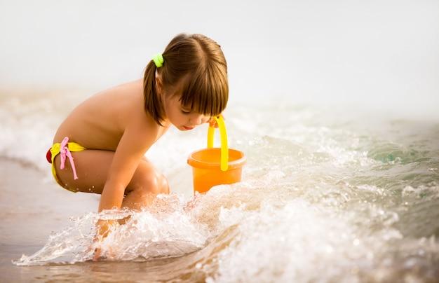 Het kleine meisje spelen met speelgoed in zeewaterrand
