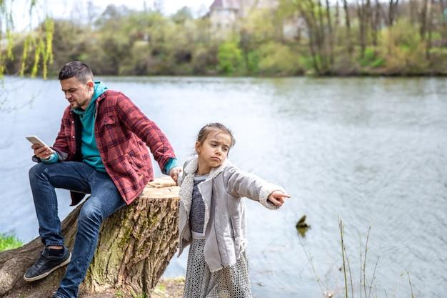 Het kleine meisje trekt vader mee voor een wandeling, maar hij kijkt op zijn telefoon en let niet op.