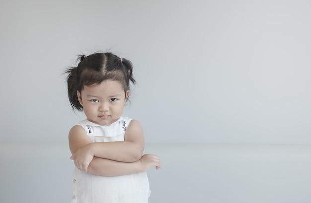 Het kleine meisje van close-up ziet er niet tevreden uit met iets