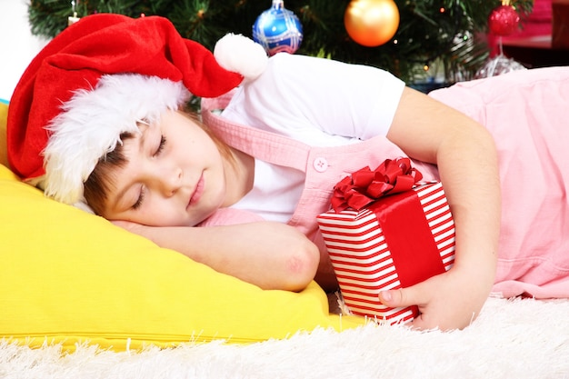 Het kleine meisje viel in slaap met een cadeau in hun handen in een feestelijk versierde kamer