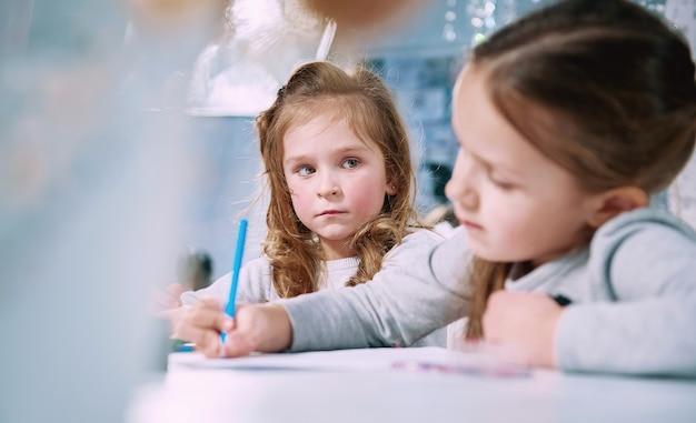 Het kleine meisje was boos op zijn vriendin en kijkt haar verdrietig aan