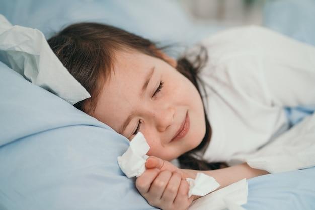Het kleine meisje werd verkouden. kinderen niezen in een zakdoek. het kind is ziek en wordt thuis behandeld. seizoensgebonden verkoudheid bij kinderen.