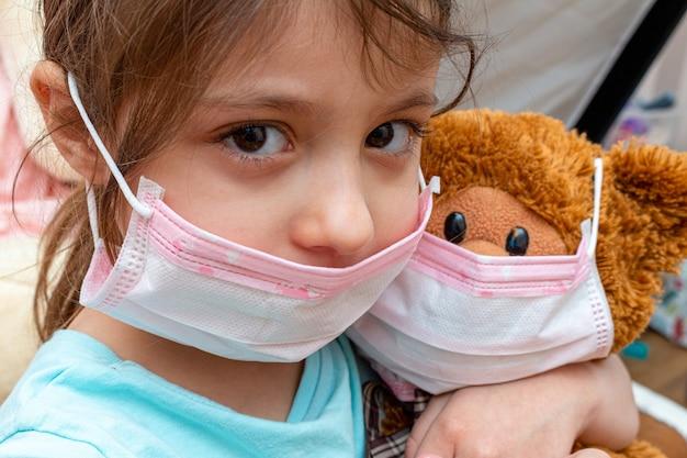 Het kleine meisjes speelstuk speelgoed draagt in medisch beschermend masker tijdens quarantaineisolatie