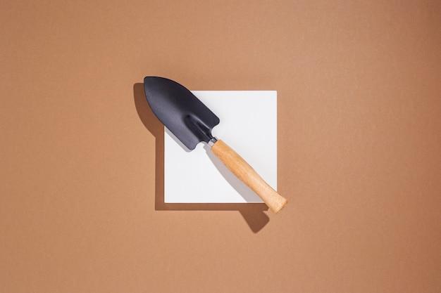 Het kleine mes van tuingereedschap ligt op een wit vierkant podium op een bruine achtergrond. bovenaanzicht, plat gelegd.