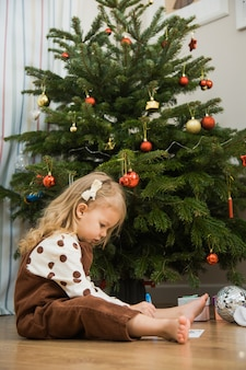 Het kleine peutermeisje zit op vloer en schrijft of tekent brief voor santa. schattige jongen doen thuis wens op kersttijd.