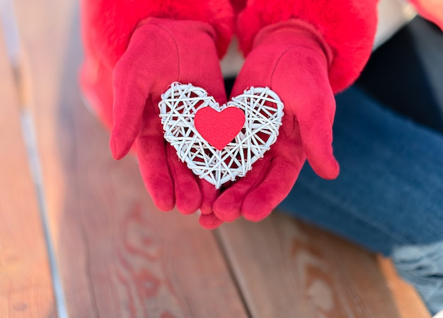 Het kleine rode hart op wit rotanhart dient in vrouw rode handschoenen op houten in.