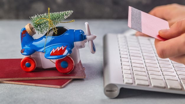Het kleine vliegtuig met kerstboom, paspoorten, toetsenbord op grijze vrouwenhand neemt creditcard
