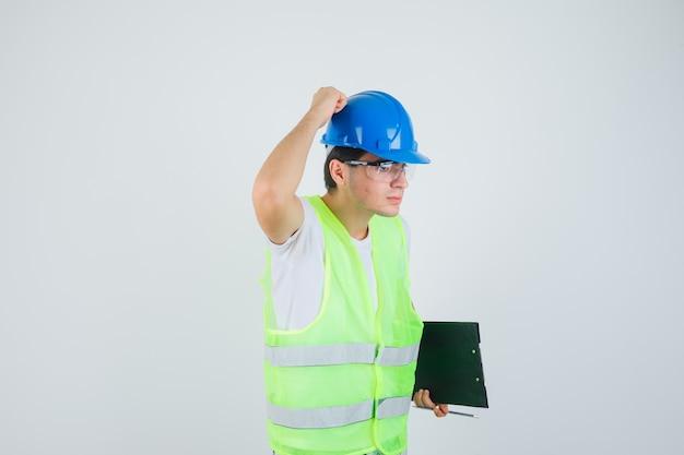 Het klembord en de pen van de jongensholding, hand op helm in bouwuniform zetten en ernstig, vooraanzicht kijken.