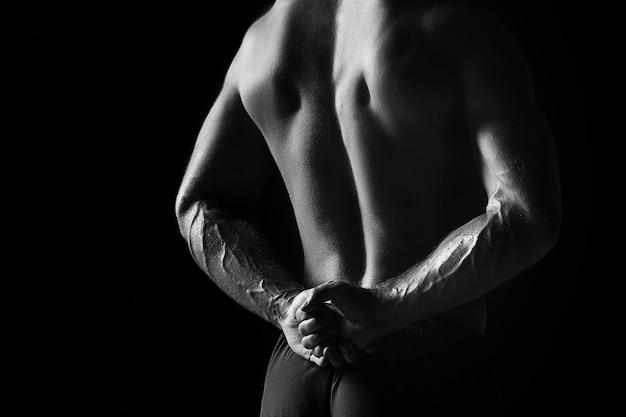 Het kleurloze beeld van de achterkant van de romp van een aantrekkelijke mannelijke lichaamsbouwer op een zwarte studioachtergrond.